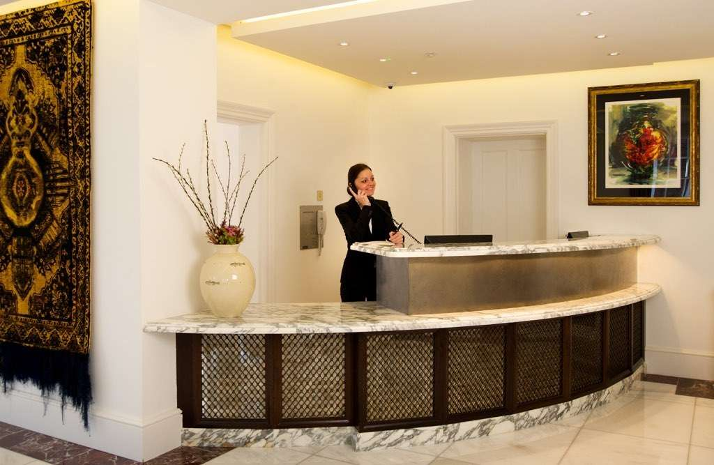 Reception desk with receptionist smiling behind it
